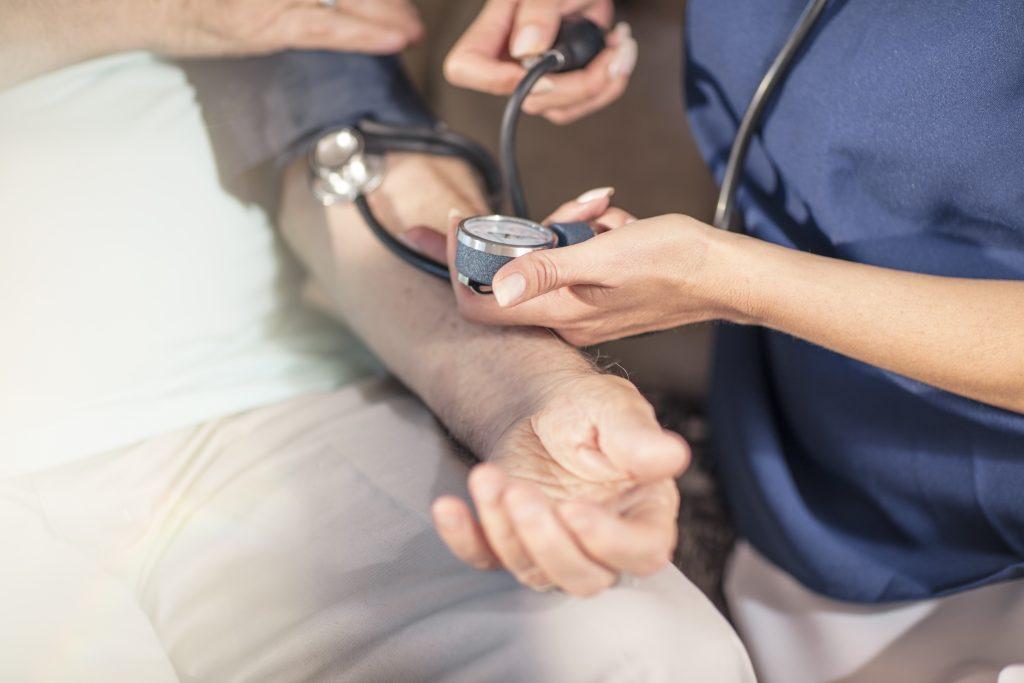 cuidando de todos foto de uma enfermeira medindo a pressão arterial de um paciente